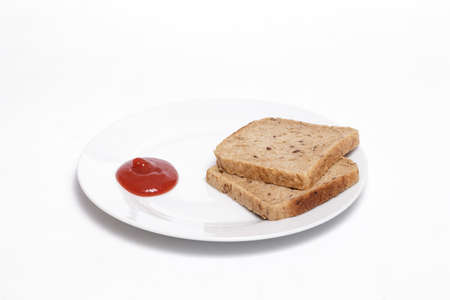 Full grain bread slices on a white dish against white background. Helathy, vegan food concept.