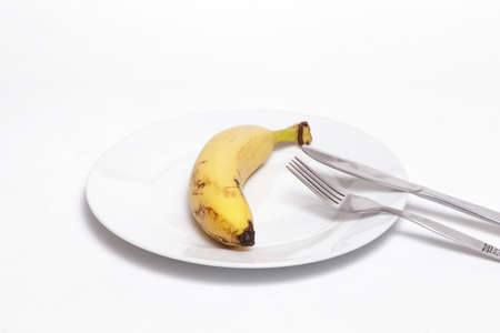 Banana and cutlery on a white dish against white background. Helathy, vegan food concept.