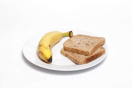 Banana and full grain bread slices on a white dish against white background. Helathy, vegan food concept.