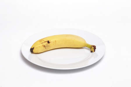 Banana on a white dish against white background. Helathy, vegan food concept. Stockfoto