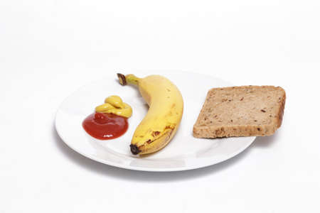 Ketchup, mustard, banana and full grain bread slices on a white dish against white background. Helathy, vegan food concept.