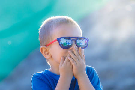 Young white preschool 4 years old boy in sunglasses is surprised or frightened on a sunny summer day.