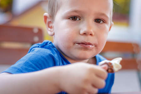 Young white preschool 4 years old boy looking at the camera while eating icecream on a summer day.