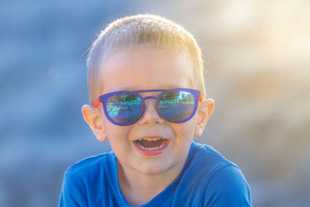Young white preschool 4 years old boy in sunglasses happily laughing while looking at the camera on a sunny summer day.