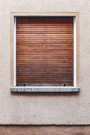 Old building exterior in Bamberg, Germany. Window with closed wooden shutter. Warm colors, minimalistic design. Home, architecture concept.