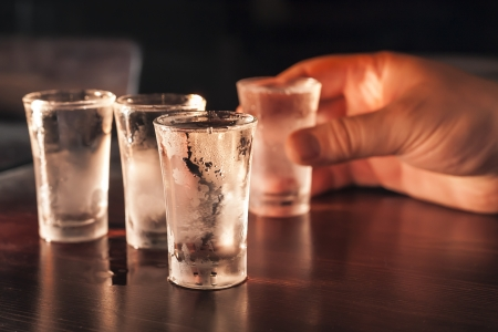 life threatening: Three full shot glasses of vodka on a wooden table