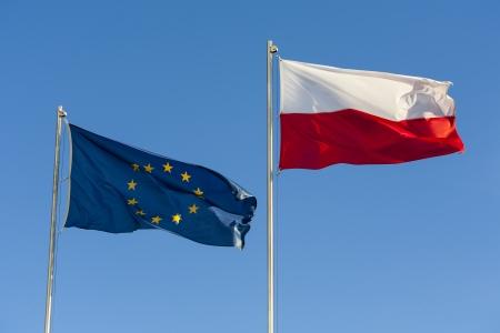 polish flag: European Union flag and a Polish flag on a background of clear sky  Stock Photo