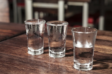 life threatening: three full shot glass of vodka on a wooden table