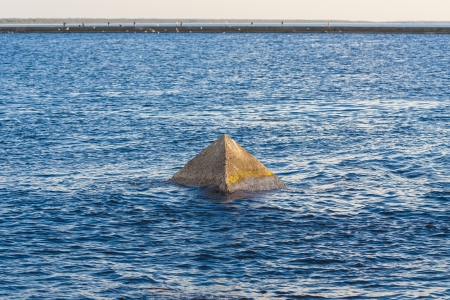 A stone pyramid protruding from the water, the view of the blue sea with small waves. photo