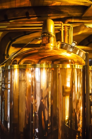 Large, copper container for brewing, many reflections of light  photo