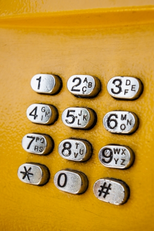 Metal keypad with numbers, part of yellow public phone on the street  photo