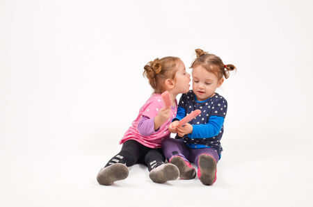 Twin girls eating ice cream and kissing photo