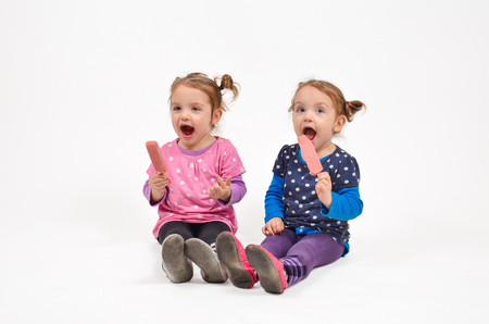 rewarding: Twin girls eating ice cream and enjoying each others company