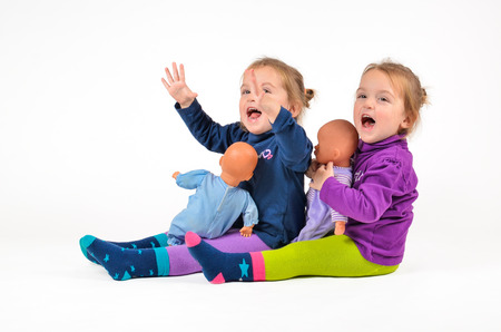 Twin Babies with Dolls playing and laughing photo