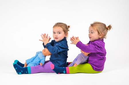 遊んで、笑っている人形と双子の赤ちゃん 写真素材