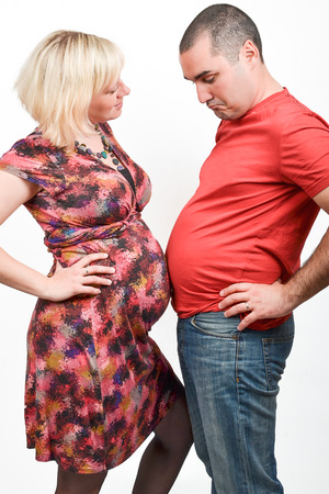 A husband is experiencing Couvade syndrome or Sympathetic pregnancy photo