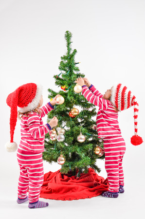 Twin babies decorating a Christmas Tree photo
