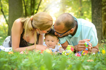 Happy interracial family is enjoying a day in the park photo