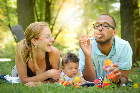 mixed family: Happy interracial family is blowing bubbles Stock Photo