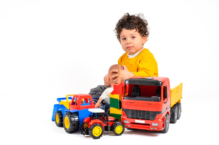Child with surplus of different kind of toys is content