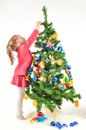 Little Girl is decorating Christmass Tree with home made Ornaments isolated on white Background photo