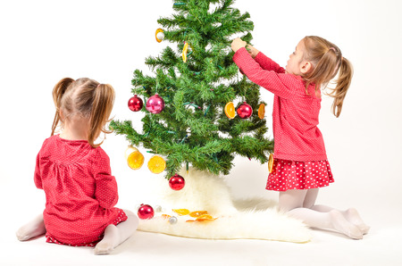 Twin Girls are decorating Christmass Tree with home made Ornaments isolated on white Background photo