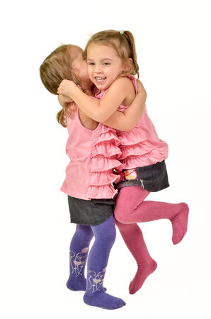 Twin Girls are celebrating, jumping and hugging like happy children photo