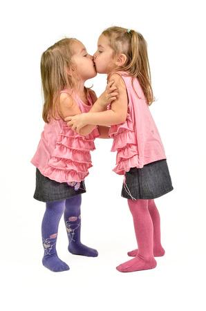 niñas gemelas: Dos niñas que besan. Aislado en blanco