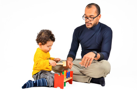 Father and son are playing together as part of the didactic autism children therapy