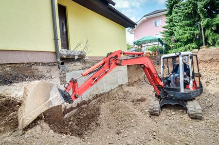 油圧ショベルの助けを借りて、大きな家族の家を再構築中です。 写真素材 - 36172445