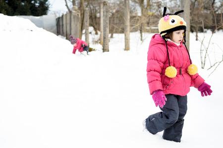 niñas gemelas: Dos niñas gemelas están jugando en la nieve. Vestido con ropa de invierno.