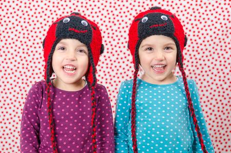 niñas gemelas: Muchachas gemelas están sonriendo a la cámara y ser feliz. Los niños pequeños son alegres. Niño lleva un gorro de lana en forma de mariquita en un fondo con puntos rojos. Niños felices Foto de archivo