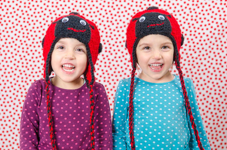 Twin girls are smiling at the camera and being happy. Little children are joyful. Child is wearing a woolen cap in the shape of ladybird on a background with red dots. Happy Children