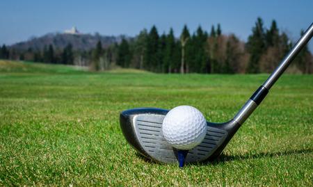 chofer: astillado de una pelota de golf en el verde con el club de golf conductor. Hierba verde con bosque y un castillo en el fondo. El enfoque suave o la profundidad de campo. Foto de archivo