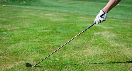trajectory: A hand is holding a golf club and measuring the Trajectory. Green grass, white glove with shallow depth of field