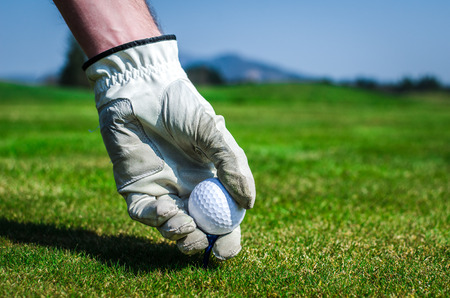 Hand with a glove is placing a tee with golf ball in the ground. Golf course with green grass with mountains in the background. Soft focus or shallow depth of field. photo