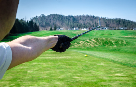 trajectory: Golfer is pointing witha a golf club. Showing a direction and measuring the trajectory. Green grass golf course Stock Photo