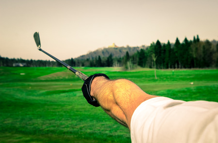 trajectory: Golfer is pointing witha a golf club. Showing a direction and measuring the trajectory.