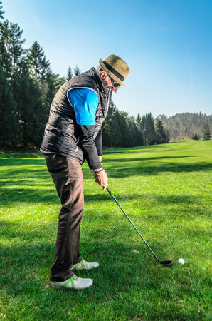 stay in green: Senior citizen is playing golf. Active retirement. A man is golfing to stay in shape. On green grass with woods in the background