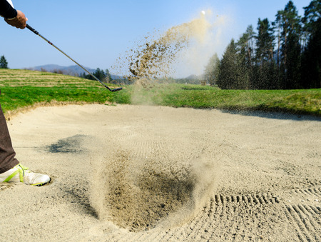 Golfer hitting out of a sand trap. The golf course is on the sand. Sand making splashes Standard-Bild
