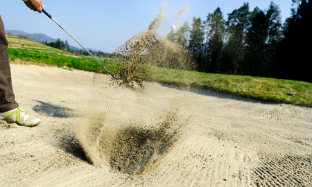 Golfer hitting out of a sand trap. The golf course is on the sand. Sand making splashes Stock Photo