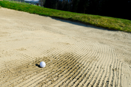 bogey: Golf ball i strapped in sand bunker on the golf course