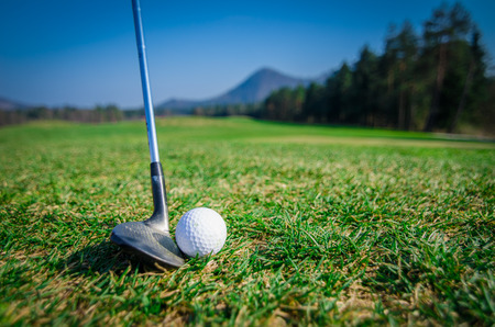 chipping a golf ball onto the green with driver golf club. Green grass with forrest and mountains in the background. Soft focus or shallow depth of field. Side view 写真素材