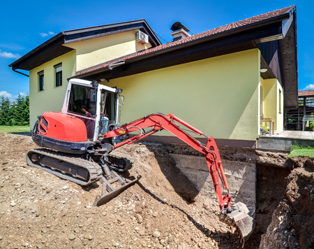 bulldozer: A family house is being rebuilt and renovated with the help of an excavator. Digger is digging dirt and excavating the basement.