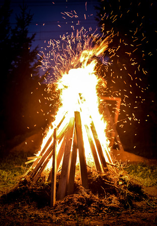Big bonfire and sparks in the night. Orange fire is reaching for the sky. Forrest and trees in the background Stock Photo