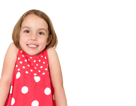 Little girl in red dress with white dots is shrugging and smiling. Place for your text or logo