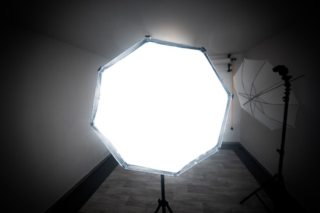 Deep octobox studio softbox modifier with studio umbrella in the back is shooting at the viewer in a professional photo studio.