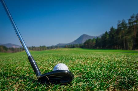 ドライバー ゴルフ クラブとグリーンにゴルフ ・ ボールをチッピングします。緑の森と山を背景に草。ソフト フォーカスまたはフィールドの浅い深さ。背面図 写真素材 - 40443594