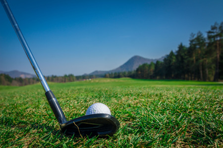 Chipping a golf ball onto the green with driver golf club. Green grass with forrest and mountains in the background. Soft focus or shallow depth of field. Back view Stock Photo