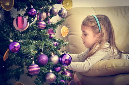 chrismas: Little Girl is decorating Christmas Tree with home made Ornaments in retro filter effect